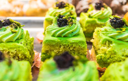 Squares of pastry cream, pistachio, bright green, red currants. Sicily Stock Photos