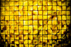 Squares Yellow. Close up picture of a painted wall with bright yellow squares with antiqued finish Royalty Free Stock Photo