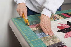 Squaring up a piano keys border. A quilter using a rotary cutter and ruler to trim excess fabric off of the piano key border Stock Image