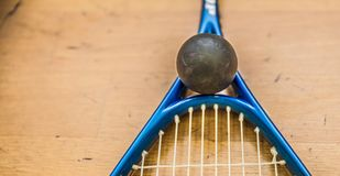 Squash ball on court with squash racket ready to play new game stock images