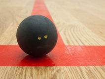 Squash ball on t-line. Double yellow dot official black squash ball on the red t-line in squash court Royalty Free Stock Photography