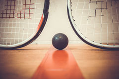 Squash ball between two squash rackets royalty free stock image