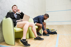 Squash businessmen players. Businessmen are squash players changing their clothesfor having match in squash. One men talking over mobile phone. Business and Stock Image