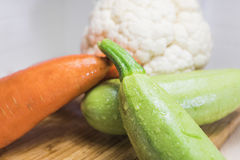 Squash cauliflower and carrots on a cutting board Stock Photo