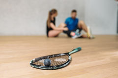 Squash game concept, racket with ball. Young couple sitting on the floor after training, indoor sport club stock images