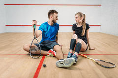 Squash game concept, young couple, rackets, ball. Squash game concept, rackets with ball, young couple sitting on the floor after active training, indoor sport stock image