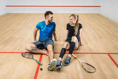 Squash game concept, young couple, rackets, ball. Squash game concept, rackets with ball, young couple sitting on the floor after active training, indoor sport Royalty Free Stock Photo