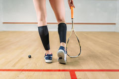 Squash game female player legs, racket and ball Stock Photos