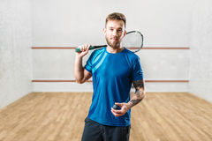 Squash game player with racket and ball in hands. Squash game male player with racket and ball in hands, indoor training court on background Stock Images