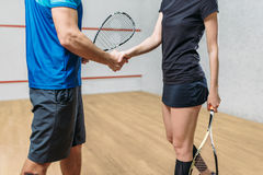Squash game players with rackets shake hands. Male and female squash game players with rackets shake hands. Young couple in sportswear with racquets, indoor Stock Photography