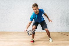 Squash game training, male player with racket. And ball, indoor court on background Stock Photo