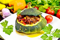 Squash green stuffed with meat and vegetables on dark board Royalty Free Stock Photo