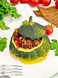 Squash green stuffed with meat and vegetables on light board Stock Photos