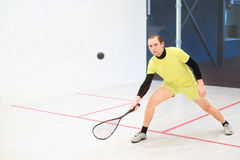 Squash player in action. Young caucasian squash player hitting a ball in a squash court. Squash player in action. Man playing match of squash Stock Photography