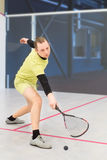 Squash player in action. Young caucasian squash player hitting a ball in a squash court. Squash player in action. Man playing match of squash. Sports activities Stock Photo
