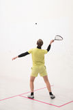 Squash player back view. Back view of squash player hitting a ball in a squash court. Squash player in action. Man playing match of squash Stock Photo