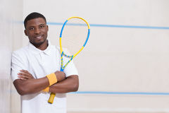 Squash player on cort. Male squash player posing for photographer  against white background. Happy smiling black man on squash court Royalty Free Stock Images
