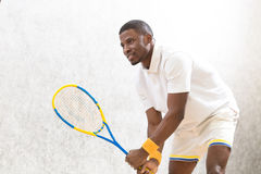 Squash player man. Male tennis player holding racquet on court. Handsome man playing squash game indoors. Sports concept Stock Images