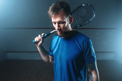 Squash player with racket, indoor training court. Male squash player with racket, indoor training court on background. Active sport with racquet Royalty Free Stock Photos