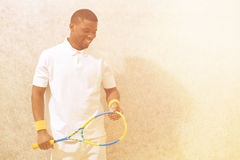 Squash player. With racquet  on white background. Happy black man smiling and looking down on squash court Royalty Free Stock Photos