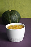Squash puree. Bowl of squash puree (soup) and acorn squash Royalty Free Stock Photography