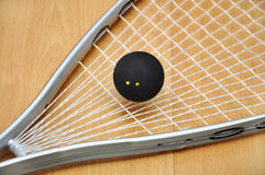 Squash racket and ball. Close up of a squash racket and ball over wooden background stock image