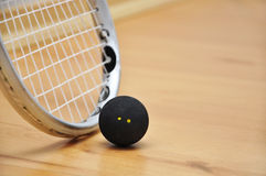 Squash racket and ball. Close up of a squash racket and ball over wooden background stock photography