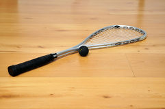 Squash racket and ball. A squash racket and ball on the floor royalty free stock images