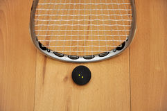 Squash racket and ball. Close up of a squash racket and ball on wooden floor stock photos