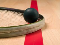 Squash racket and ball. On a red line Royalty Free Stock Photos