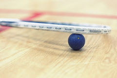 Squash racket and ball. Close up of a squash racket and ball on the wooden background. Racquetball equipment. Squash ball between squash racket and floor on the royalty free stock photo