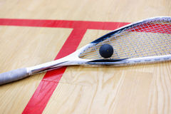 Squash racket and ball on the court. Squash racket and ball on the wooden background. Racquetball equipment. Squash ball and squash racket on the court next to a Stock Photography