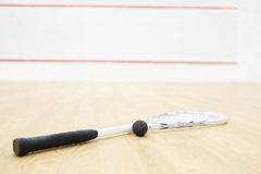 Squash racket and ball. Racquetball equipment on the court and wall with red lines on the background. Photo with selective focus royalty free stock photography
