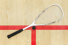 Squash racket and ball view from above. Squash racket and ball on the wooden background view from above . Racquetball equipment on the court near red line royalty free stock photos