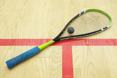 Squash racket and ball. On the wooden background. Racquetball equipment on the court near red line. Photo with selective focus Royalty Free Stock Image