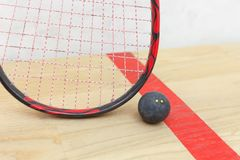 Squash racket and ball. On the wooden floor. Closeup racquetball equipment on the court near red line. Photo with selective focus royalty free stock photos