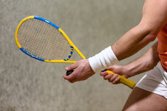 Squash racket closeup. Half closeup picture of squash racket in man's hands. Muscular man playing squash on court indoors Royalty Free Stock Photography