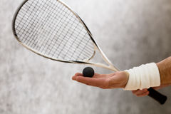 Squash racket closeup. Closeup of squash racket and one ball in man's hand. Black-coloured ball represented on man's hand who is on court royalty free stock images