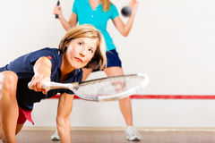 Squash racket sport in gym. Two woman playing squash as  racket sport in gym Stock Image