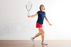 Squash racket sport in gym, woman playing. Mature woman playing squash as racket sport in gym, it might be a competition Royalty Free Stock Image