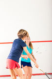 Squash racket sport in gym, women competition. Two women playing squash as racket sport in gym, it might be a competition Stock Photography