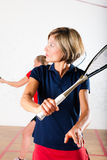 Squash racket sport in gym, women competition. Two women playing squash as racket sport in gym, it might be a competition Royalty Free Stock Image