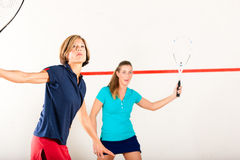 Squash racket sport in gym, women competition. Two women playing squash as racket sport in gym, it might be a competition Royalty Free Stock Photography