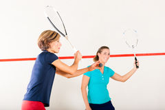 Squash racket sport in gym, women competition. Two women playing squash as racket sport in gym, it might be a competition Stock Photo