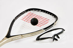 Squash racquet, ball and safety glasses. Closeup of a squash racquet, ball and safety glasses, isolated against a white background stock image