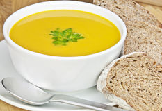 Squash soup. A bowl of squash soup and sliced bread Royalty Free Stock Photography