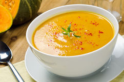 Squash Soup. A bowl of creamy squash soup garnished with rosemary and paprika Royalty Free Stock Photos
