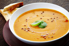 Squash soup with basil leaf Stock Photography