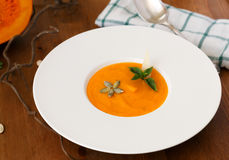 Squash soup in a plate with basil leaf Stock Photo