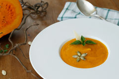 Squash soup in a plate with basil leaf Royalty Free Stock Photography